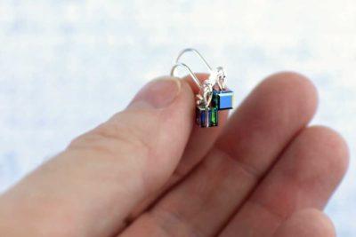 Little black pixel earrings in hand for scale, by PurlsAndPixels