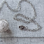 Silver yarn necklace with ruler for scale