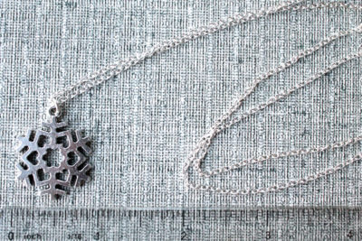 Long silver snowflake necklace for scale